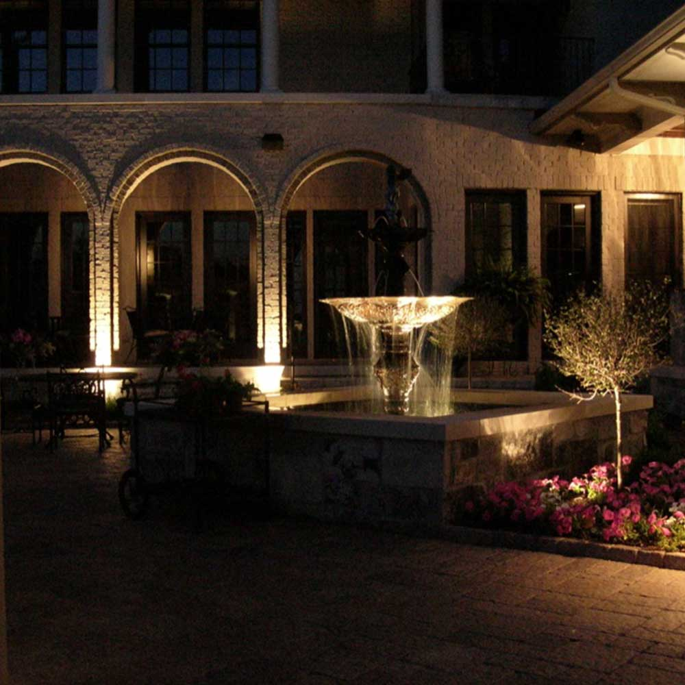 custom outdoor lighting illuminating water fountain and front of home