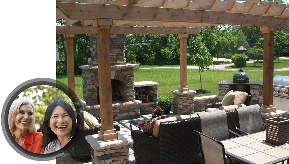 gull outdoor living space with stone fire place and two women smiling