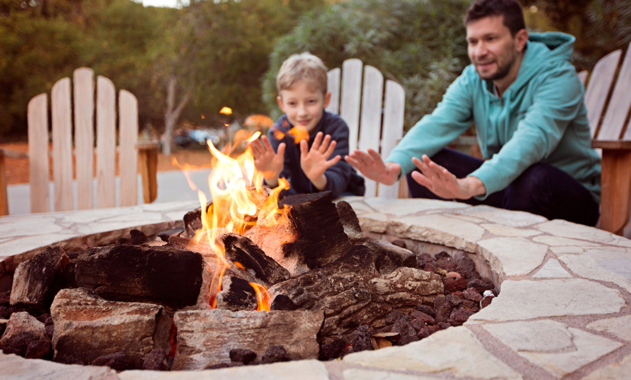 father and son warming hands by outdoor stone fire pit